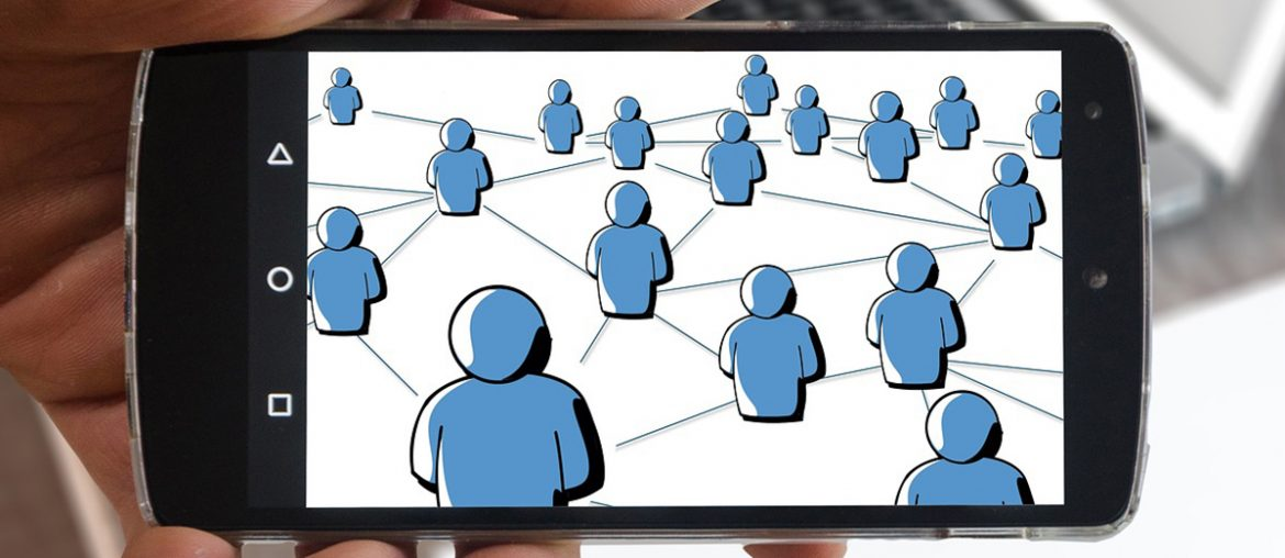 A hand holding a smartphone containing an image of multiple blue figures connected in a web.
