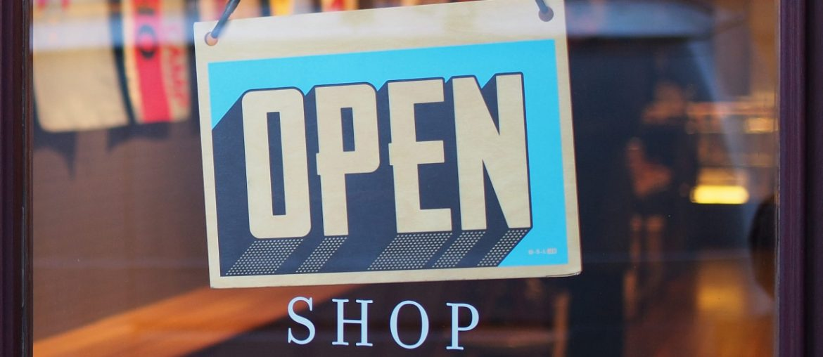 "An open sign hangs from a glass door to a business directly above the word ""shop."""