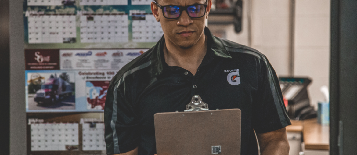 Man holding a clipboard with a serious look on his face and multiple calendars hanging on the wall in the background.