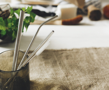 A recycled wine bottle converted into a drinking glass holds three reusable metal straws and a small bottle brush, atop a burlap mat with a houseplant in the background.