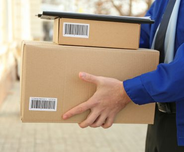 A courier dressed in a blue jacket carries packages up to a doorstep. Only the courier's hands and torso are visible.