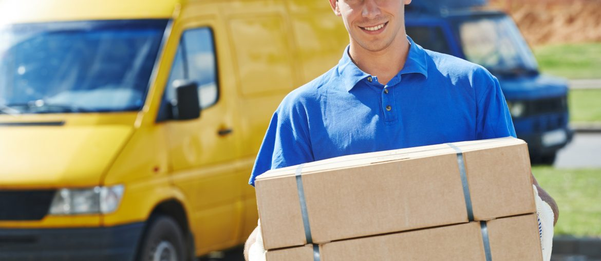 A delivery driver dressed in a blue polo shirt and a blue hat is holding two cardboard boxes. They are standing in front of a yellow delivery van.