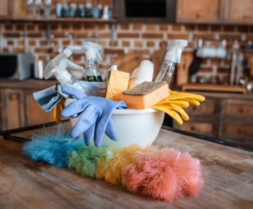 A white bowl full of cleaning supplies sits on top of a dusty wooden table. In the foreground, there is a rainbow colored duster. In the background, a wooden kitchen counter with various appliances is visible.