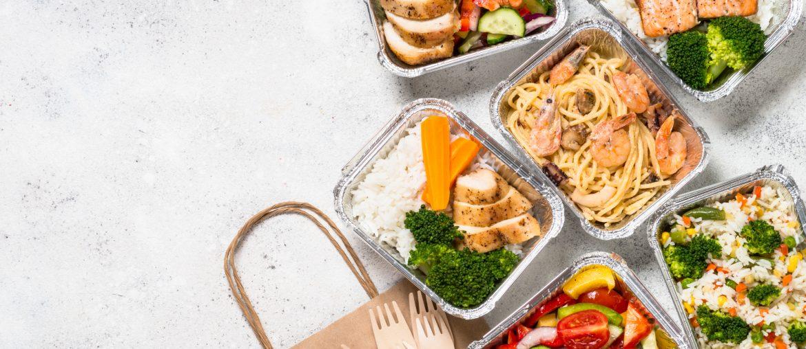 Overhead view of several individual meals packaged in tin foil containers, next to a brown paper delivery bag and several plastic forks.