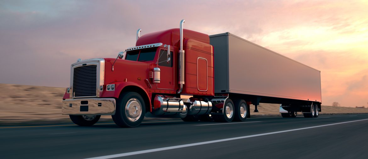 A red semi-truck with a white trailer is driving on the highway. Dry terrain and a slightly cloudy sunset are visible in the background.